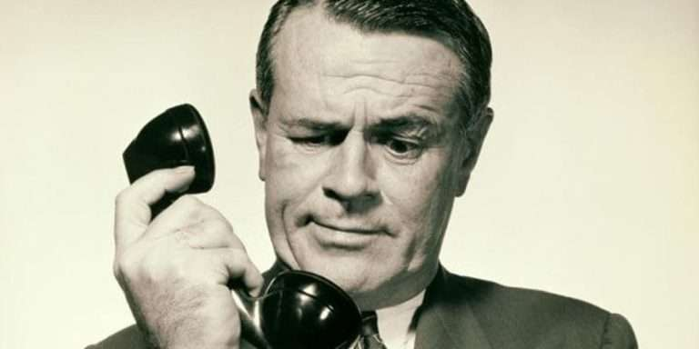 Man looking at old style telephone